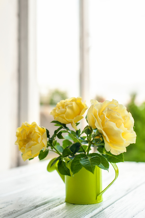 Bouquet of yellow roses in metal cup on the window in the sunshine. Shallow DOF, soft focus, vertical composition.