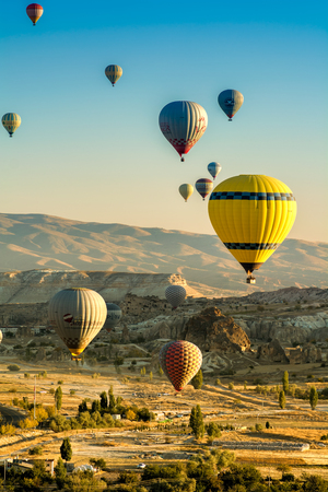 Goreme, Turkey - October 4, 2016: The great tourist attraction of Cappadocia - balloon flight at sunrise on 4th of October, 2016. Cappadocia is known around the world as one of the best places to fly with hot air balloons. Goreme, Turkey. Editorial