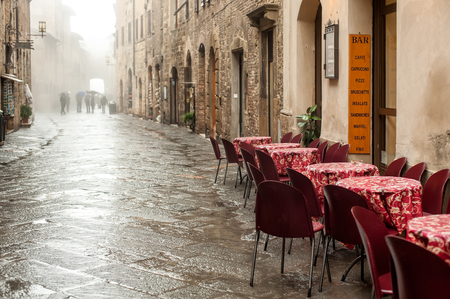 europeans: Empty restaurant chairs and tables in the street after rain, San Gimignano city in Tuscany, Italy.