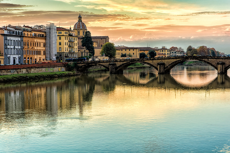 The Ponte alla Carraia at sunset, is a five-arched bridge spanning the River Arno and linking the district of Oltrarno to the rest of the city of Florence, Italy. With Chiesa di San Frediano in background.