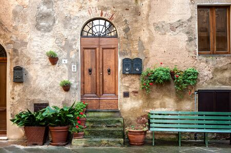 pienza: The old town and the streets of the medieval period,  Pienza, Italy. House facade view with door, window and bench.
