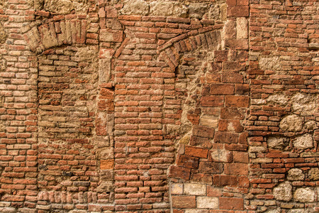 costruction: Texture of typical Italian old stone and brick wall. Traces of the pledged old windows.