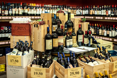 San Gimignano, Italy - November 18, 2016: Wine bottles on shop stand on 18 of November, 2016 in San Gimignano, Tuscany, Italy. Tuscany is home to some of the world's most notable wine regions. Editorial