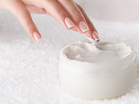 handcare: Woman applying body cream. Close-up composition of hands with white jar isolated on white background. Horizontal composition.