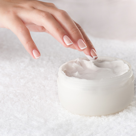 handcare: Woman applying body cream. Close-up composition of hands with white jar isolated on white background. Square composition.