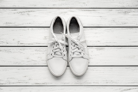 Youth classic white leather sneakers on wooden whute background. Standard-Bild