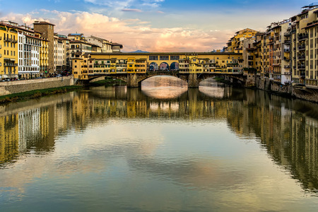 river arno: Ponte Vecchio, old bridge, medieval landmark on Arno river and its reflection. Florence, Tuscany, Italy.