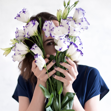 shallow dof: Woman holding a bunch of purple and white eustoma flowers behind her face. No face. Unrecognisable. Close-up. Shallow DOF.