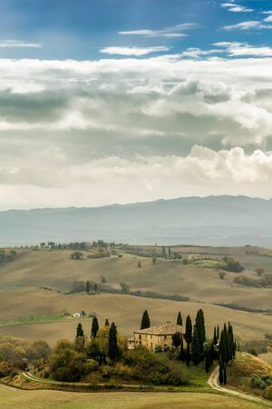 pastoral scenery: Lonely farmhouse with golden meadow hills. Tuscan autumn landscape. Tuscan Villa on countryside, San Quirico d´Orcia, Tuscany, Italy. Vertical composition with blue sky.