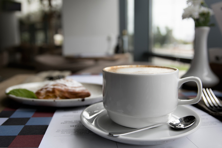 Cup of Cappuccino and cake in cafe, shallow DOF. Coffee shop cafe Interior with table. Stock Photo