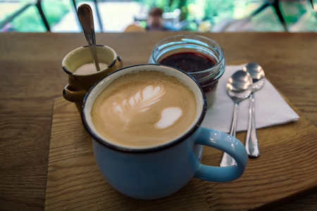 Сappuccino or coffee in blue cup and panna cotta on wooden table background. Concept photo top view, shallow DOF.