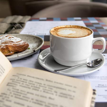 Still life details, cup of Capuccino and cake with book on table in coffee shop cafe, shallow DOF.