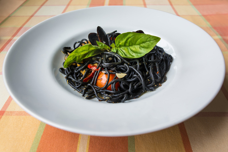 Italian black spaghetti with cuttlefish ink, mussels, tomatoes and green basil on the table with orange plaid tablecloth at sunlight. Stock Photo