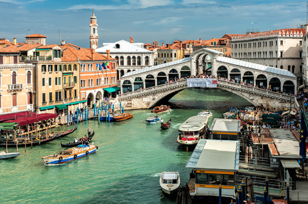 VENICE, ITALY - SEPTEMBER 26, 2012: Gondolas and tourist boats traffic on the Grand Canal with Rialto bridge in background on 26 September 2012 in Venice, Italy.