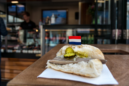 Traditional dutch snack, seafood sandwich with herring, onions and pickled cucumber. Broodje haring on the wooden table. With flag of Netherlands.