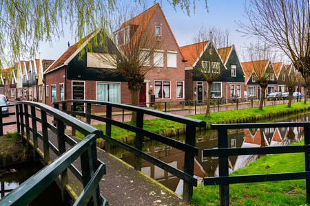 Traditional houses near canal in Holland town Volendam, Netherlands, in a spring day, with bridge on the foreground.