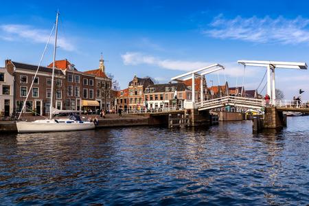 HARLEM, NETHERLANDS - APRIL 14, 2018: Spaarne river with boats, famous tourist landmark Gravestenenbrug bridge and houses in Haarlem, Netherlands.