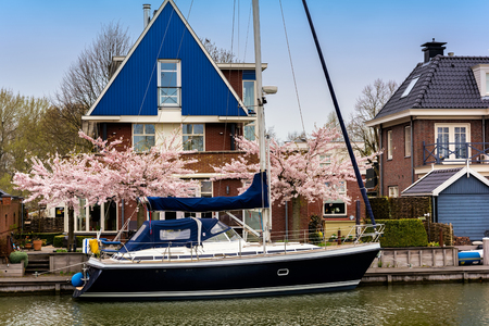 EDAM, NETHERLANDS - APRIL 14, 2018: Traditional dutch house with yacht and blooming spring tree on the canal waterfront. Edam is a small village in the district Nordholland, Netherlands.