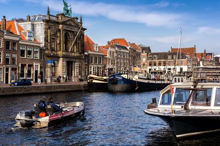 HARLEM, NETHERLANDS - APRIL 14, 2018: Spaarne river with boats and houses in Haarlem, Netherlands.