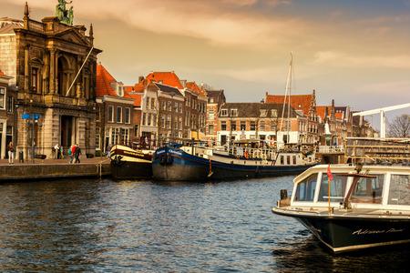 HARLEM, NETHERLANDS - APRIL 14, 2018: Spaarne river with boats and houses at sunset in Haarlem, Netherlands.