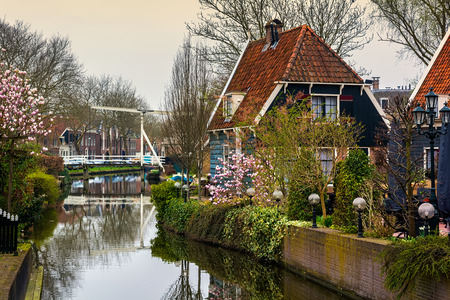 House with blooming spring trees on the canal in a small city Edam in Netherlands. Edam is a small village in the district Nordholland, Netherlands.