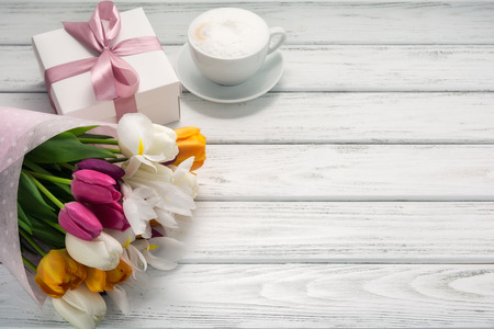 Bouquet of multicolored tulips in paper wrapper, gift box, cappuccino coffee with milk froth on white wooden table. Copy space. Beautiful breakfast on Mothers or Woman's day. Banco de Imagens