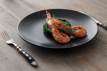 Two shrimps on spinach in black plate. Angle view, studio shot. Photo taken on the workshop.