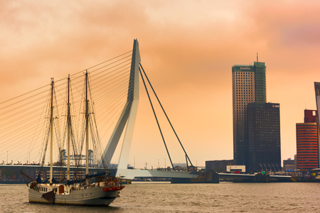 ROTTERDAM, NETHERLANDS - APRIL 13, 2018: View on the Erasmus Bridge with vessel on foreground and cityscape during sunset, also called The Swan, on the Maas river in Rotterdam.