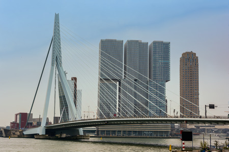 ROTTERDAM, NETHERLANDS - APRIL 13, 2018: View on the Erasmus Bridge with cityscape, also called The Swan, on the Maas river in Rotterdam. It is Holland's largest combined cable-stayed bascule bridge. Publikacyjne