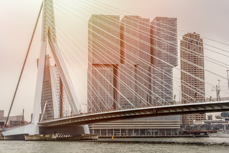 ROTTERDAM, NETHERLANDS - APRIL 13, 2018: View on the Erasmus Bridge with cityscape during sunset , also called The Swan, on the Maas river in Rotterdam.