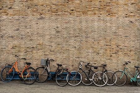 Bicycles on roadside with vintage brick wall background, with copy space. Zdjęcie Seryjne