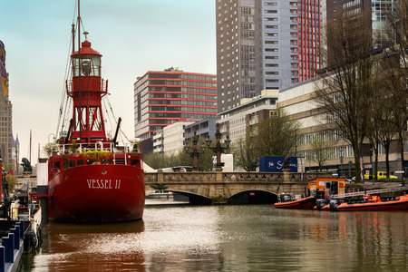 ROTTERDAM, NETHERLANDS - APRIL 13, 2018: Red vessel on river of the city Rotterdam. Buildings on background.