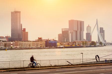 ROTTERDAM, NETHERLANDS - APRIL 13, 2018: Rotterdam embankment on the sunset with 'De Rotterdam' skyscraper and Erasmus bridge viewed from across the river Nieuwe Maas. Publikacyjne