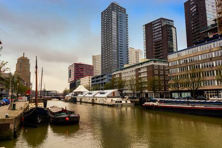 ROTTERDAM, NETHERLANDS - APRIL 13, 2018: Ships on river of the city Rotterdam. Buildings on background.
