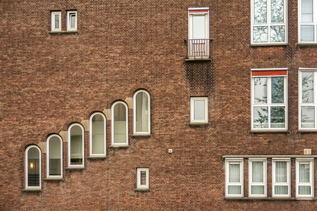 Building with a brick facade and unusual windows in city Rotterdam.