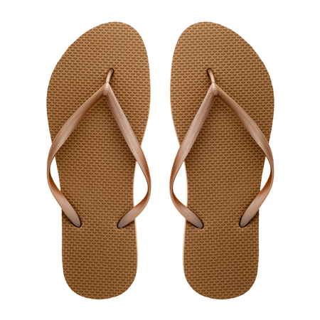 Golden rubber flip-flops isolated over white background, pair of thongs, shot above.