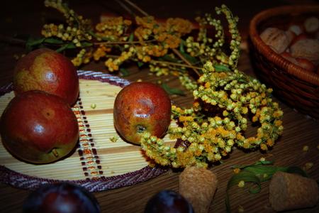 стиль жизни: Стиль жизни. Натюрморт. Состав. Осень. Груши и орехи, сушеные цветы на деревянный стол Фото со стока