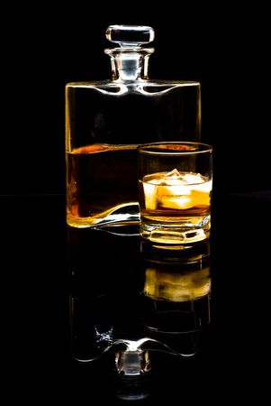 carafe of scotch whiskey or bourbon and drink with ice on black background photo