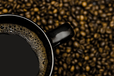 black mug of coffee and scattered beans photo