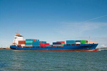 maritime: container ship coming into port Stock Photo