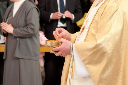 Catholic priest granting the Communion  Stock Photo - 9635226