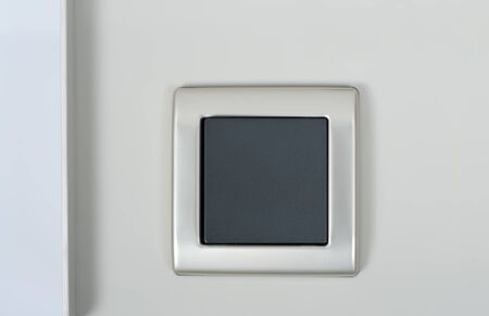 light switch on the wall with grey button on silver frame photo