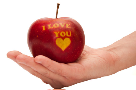 red apple with the words I love you on the open hand photo