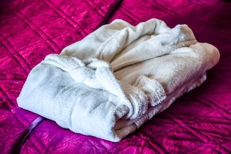 white bathrobe on the bed in hotel room photo