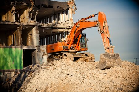 orange big digger destroys building Stock Photo