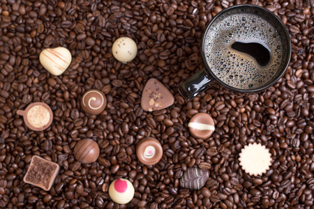 pralines: coffee beans background and black cup with pralines Stock Photo