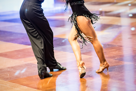 Beautiful womanish and masculine legs in active ballroom dance, indoors