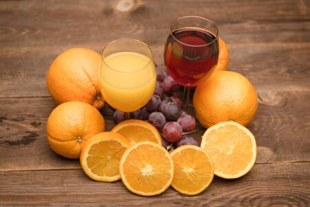 fresh orange, apple and grape juice and fruits on a wooden background