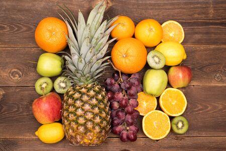 Tasty fruit background with orange, kiwi, grape, apples and lemon on the wooden table
