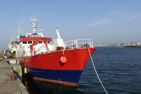 Red fishing boat moored alongside the wharf at the fishing harbor of Lorient, Brittany France. Horizontal view from bow